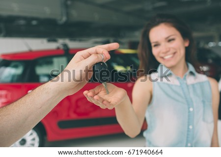 Beautiful young woman is holding a key in car dealership. Auto business, car sale, - happy female model in auto show or salon