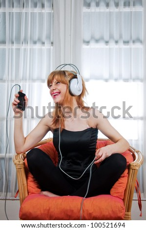 Stock photo beautiful young woman is listening to the music sitting in