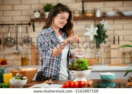 Beautiful young woman is preparing vegetable salad in the kitchen. Healthy Food. Vegan Salad. Diet. Dieting Concept. Healthy Lifestyle. Cooking At Home.