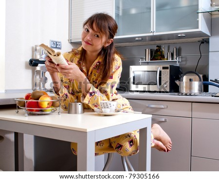 beautiful young woman is reading a book and has a breakfast. - stock photo