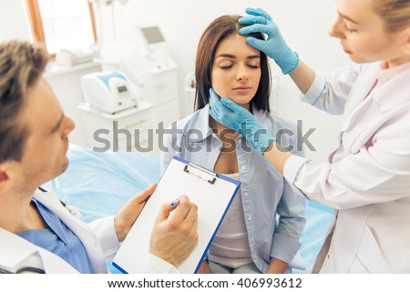Beautiful young woman is sitting with closed eyes in doctors office, two doctors are examining her face and making notes