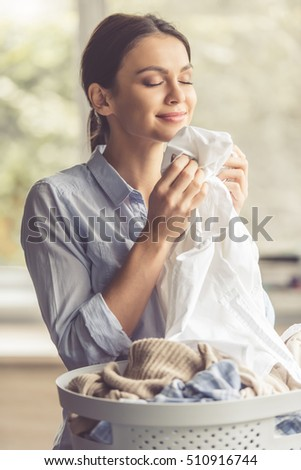 Beautiful young woman is smelling clean clothes and smiling while doing laundry at home