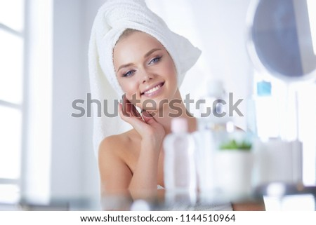 Beautiful young woman is touching her face and smiling while looking at the mirror #1144510964