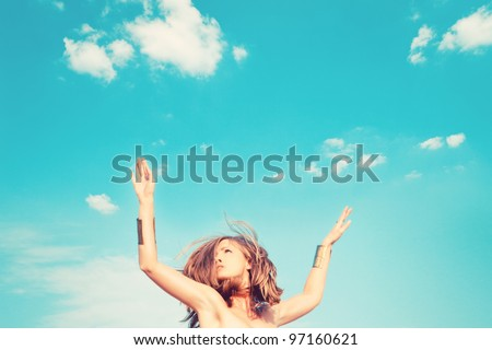beautiful young woman jump against blue sky with clouds small amount of grain added