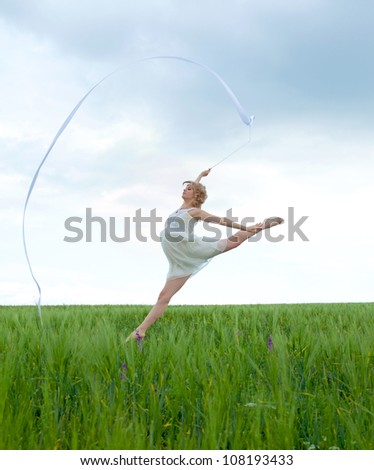 Beautiful young woman jumping on a green meadow with a gymnastic ribbon