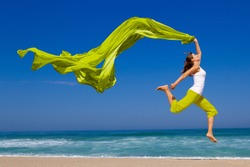 Beautiful young woman jumping on  the beach with a colored tissue