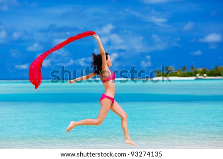 Beautiful young woman jumping on the beach with a red scarf
