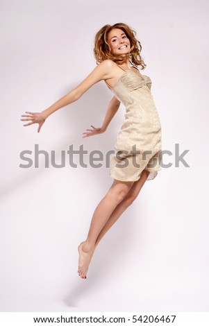 beautiful young woman jumping, studio light background