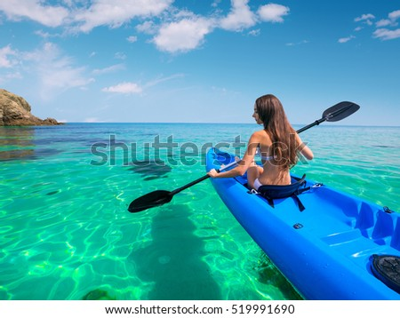 Beautiful young woman kayaking in the sea near the islands. Adventure by kayak. #519991690