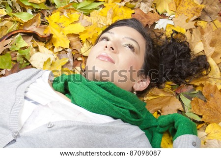beautiful young woman laying down on leaves in autumn