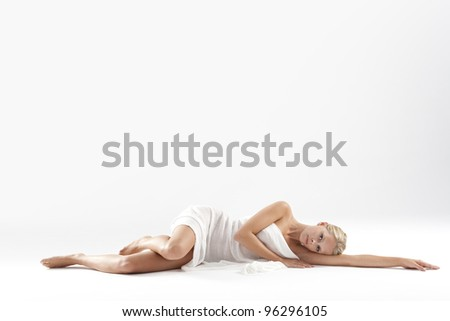 Beautiful young woman laying down with white fabric covering her body.