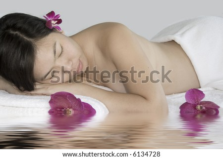 beautiful young woman laying on massage table at spa
