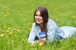 Beautiful young woman laying on the grass with cup of takeaway drink