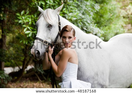 Beautiful young woman leading a grey horse in the country - stock photo