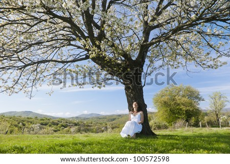 Beautiful young woman leaning on a cherry tree in bloom feeling one with Nature