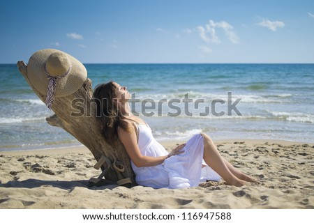 Beautiful young woman leans against a piece of driftwood on the beach