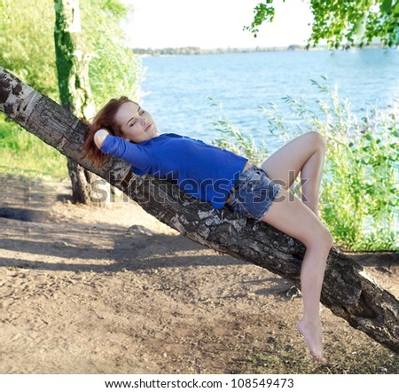 Beautiful young woman leans her back against a leaning tree besides a lake. She is wearing jeans shorts and blue shirt.