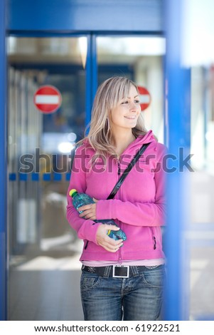 Beautiful young woman leaving a supermaket with a bottle of water