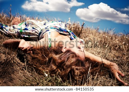 beautiful young woman lie on ground in silk dress, blue sky with clouds in background, summer sunny day