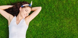 Beautiful young woman lies on the grass. Fresh natural summer concept. View from the top.