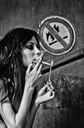 Beautiful young woman lights a cigarette near the
