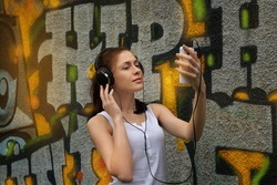 beautiful young woman listening to music with headphones on a background of graffiti