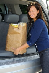 Beautiful Young Woman Loading Groceries Into Her SUV