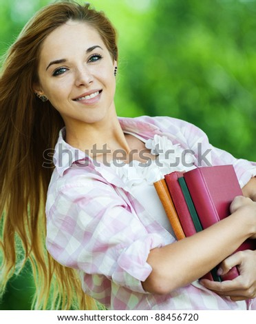 beautiful young woman long hair park holds lot books
