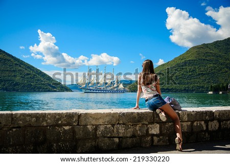 Beautiful young woman looking and waiting for amazing white sailboat at the seacoast #219330220