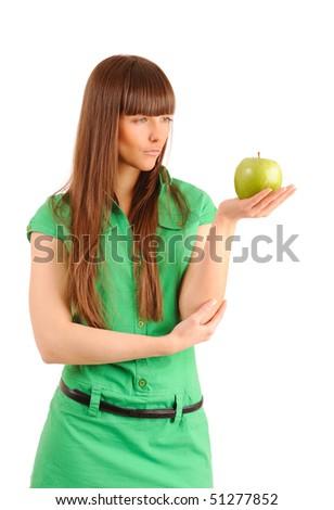 Beautiful young woman looking at a green apple, studio shot.
