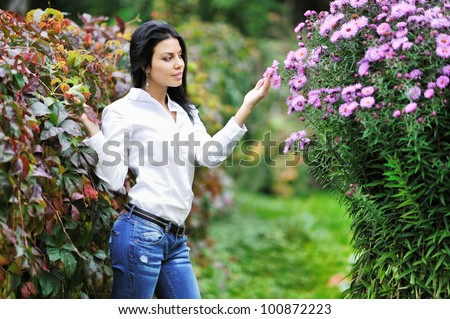 Beautiful young woman looking at flowers in a garden