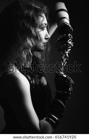 Stock Photo Beautiful young woman looking away, on her hands gloves, look very passionate. In her hands she holds a metal chain. The photo is black and white.