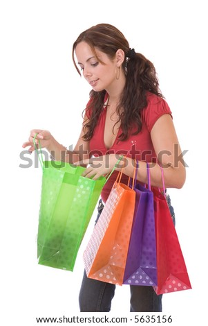 Beautiful young woman looking her shopping - over a white background