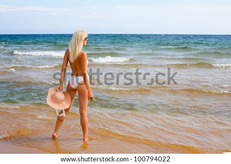 Beautiful young woman looking into the sea