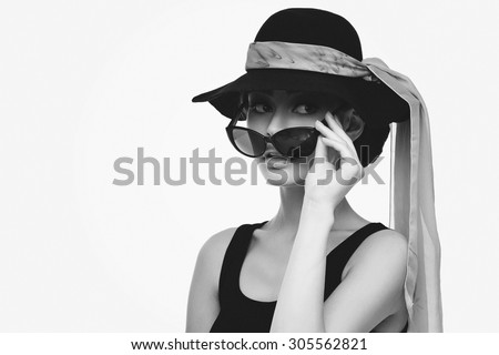 Beautiful young woman looking like Audrey Hepburn in hat with scarf and sunglasses