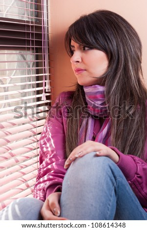 Beautiful young woman looking though a window - stock photo