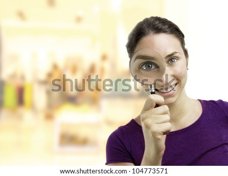 Beautiful young woman looking through a magnifying glass over a business center background