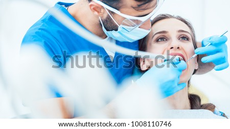 Beautiful young woman looking up relaxed during a painless dental procedure done by her reliable dentist in a modern clinic with sterile equipment