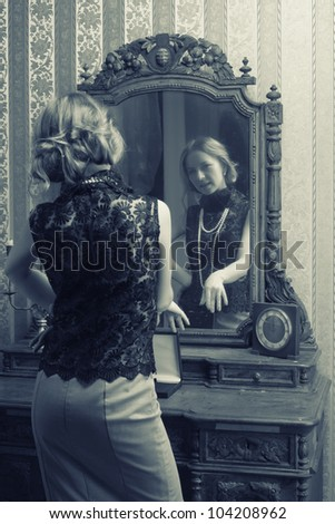 beautiful young woman looks at the reflection in the mirror in the
