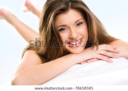 Beautiful young woman lying down and smiling looking at camera