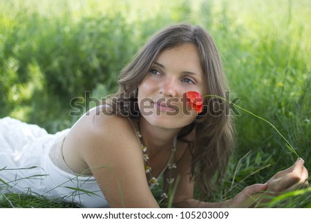 Beautiful young woman lying in a meadow with a poppy