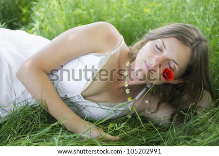 Beautiful young woman lying in a meadow with eyes closed, holding a flower