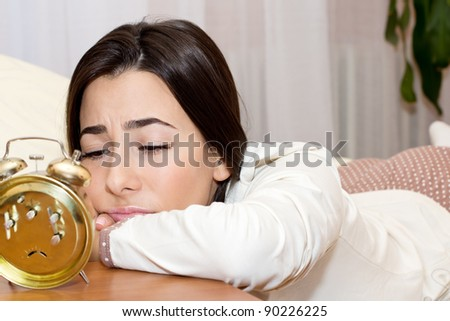 Beautiful young woman lying in the bed and tired looking in the alarm clock.