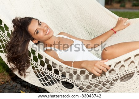 Beautiful young woman lying on a hammock in a trendy South Beach hotel in Miami.