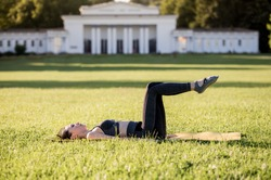 Beautiful young woman lying on a yellow mattress, pose while wearing a tight sports outfit in the park doing pilates or yoga, the hundred beginner exercises