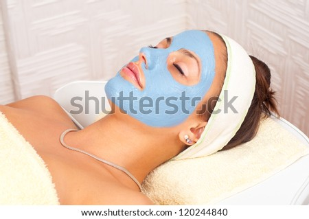 Beautiful young woman lying on massage table with natural facial mask on her face.