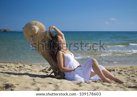 Beautiful young woman lying on sandy beach wearing a hat and a white dress enjoying the sun - stock photo
