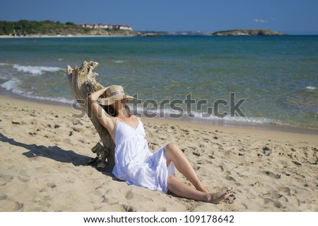 Beautiful young woman lying on sandy beach wearing a hat and a white dress enjoying the sun
