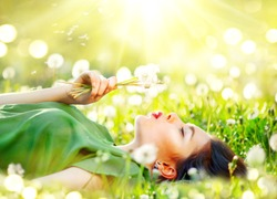 Beautiful Young Woman lying on the field in green grass and blowing dandelion. Outdoors. Enjoy Nature. Healthy Smiling Girl on spring lawn. Allergy free concept. Freedom