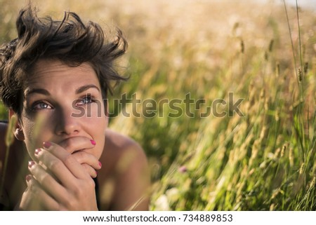 Beautiful Young Woman lying on the field in green grass being contemplative. Outdoors. Enjoy Nature. Close up.